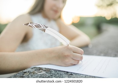boho bride writing wedding vows, old paper, feather pen, bokeh background, closeup