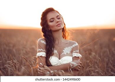 Boho schicker Stil. Porträt des böhmischen Mädchens mit weißer Kunst posiert über Weizenfeld bei Sonnenuntergang genießen. Außenfoto. Konzept der Ruhe. Lifestyle.