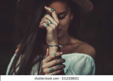 Boho chic woman in a straw hat in a white short blouse and with silver turquoise jewelry. Boho fashion. Stylish girl with silver rings using hippie style.