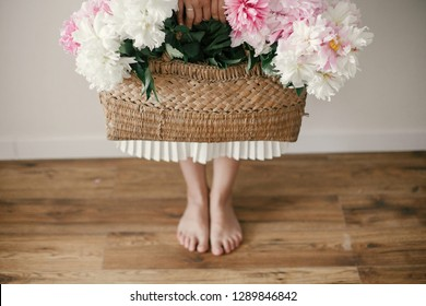 Boho girl holding pink and white peonies in rustic basket and standing barefoot on wooden floor. Stylish hipster woman in bohemian floral dress with peony flowers. International Womens Day
