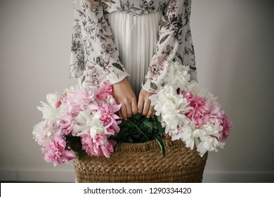 Boho girl holding pink and white peonies in rustic basket. Stylish hipster woman in bohemian floral dress gathering peony flowers. International Womens Day.  Wedding decor and arrangement