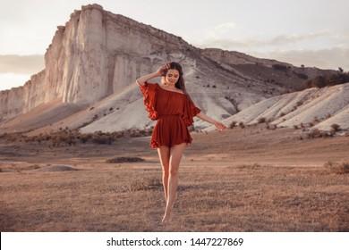 Boho Mädchen mit offenen Armen genießen Sonnenuntergang durch Weißen Felsen, Krim. Schöne Frau in rotem Kleid. Landschaftliches Bauerngut Lifestyle Outdoor Porträt. Wilder Westen. Sommerferien.