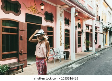 Boho girl walking on the city street. Travelling in Phuket Old Town in Thailand.
