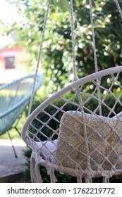 Boho hanging chair in a garden. Selective focus.