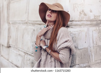 Boho jewelry on model: ethnic rings and bracelets. Beautiful woman wearing warm woolen sweater, hat and fashion jewellery. Street photo in pastel tone.