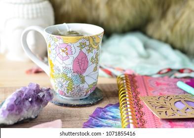 boho journal and mug setup with sage crystals and buddha