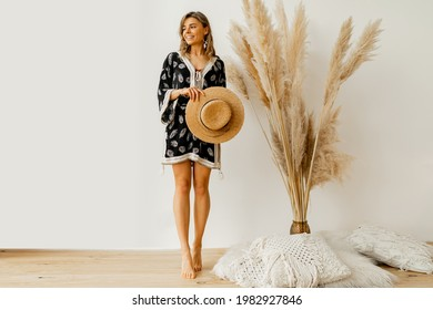 Boho mood. Stylish woman in summer outfit with straw hat posing over white background in studio with pampas grass decor.