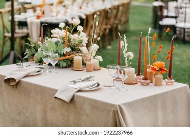 Boho, rustic, modern table design for newlyweds. Linen tablecloth and candles, flowers, accessories, glasses and plates on table outdoors on green lawn in daylight, flat lay, free space, nobody
