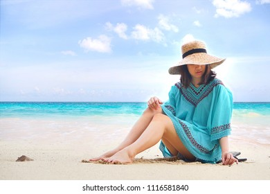 Boho style of Asian young woman relaxing on the tropical sand beach with straw hat and blue sea.Bohemian dress and beauty fashion trendy.Travel Holiday and enjoy the ocean view in summer vacation.