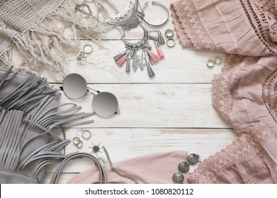 Boho style dusty pink and grey clothes and accessories on white vintage wooden background. Top view point.