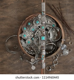 Boho style rings set on wooden sticks and bowl with assorted bohemian chic silver jewelry on wood background. Top view point.