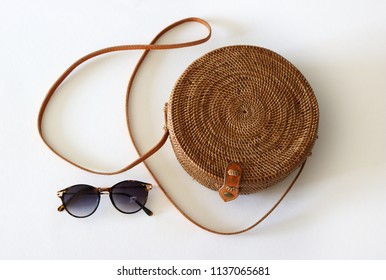 Boho style, round Ata Rattan Bag with a leather shoulder strap and sunglasses, isolated on white background.