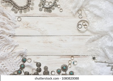 Boho style silver and turquoise jewelry set and white skirt with lace on vintage wooden background. Top view point.