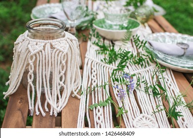 Boho style wedding reception dinning table with macrame tablecloth, decoration on a rustic wooden table