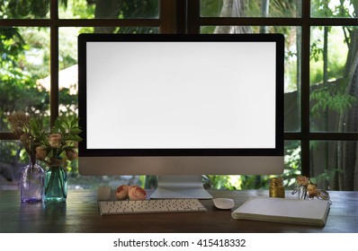 Boho style workplace. The monitor on a desk mockup scene over window. The working surface of the computer. Roses flowers, summertime, work at home concept.