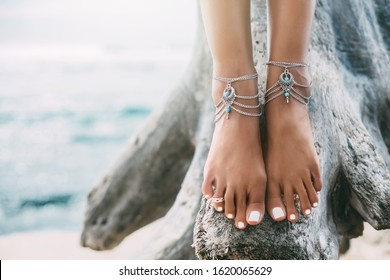 Boho styled girl wearing indian silver jewelry on the beach, tanned legs close up