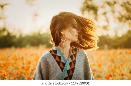 Boho stylish beautiful young woman relaxing in flower meadow on sunny summer day.