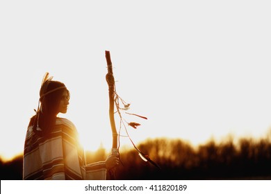 boho woman  shaman with pikestaff on background of sunset beautiful in mountains
