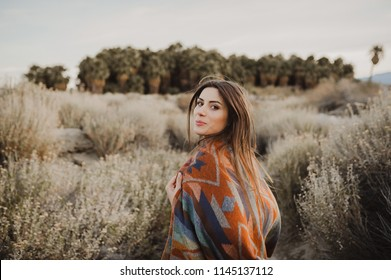 Boho woman with windy hair. Hipster girl in gypsy look, young traveler in the desert nature.