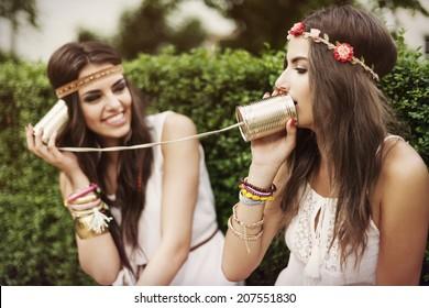 Boho women talking by tin can phone