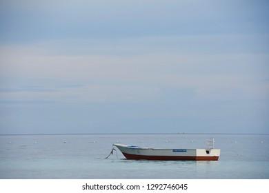 Bohol, Panglao/ Philippines - 12/23/18: Singular Floating Boat Under a Pastel Tropical Sky.