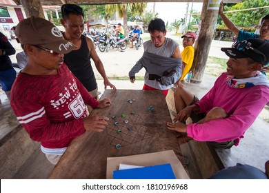 Bohol / Philippines - July 18, 2019: Filipino men playing board game with bottle caps in a park in rural area