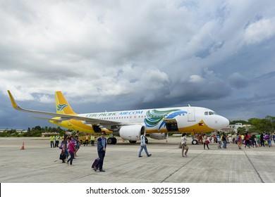 Bohol, Philippines - Jun 1, 2015: Tourists  getting on of a Cebu Pacific Air plane on Tagbilaran Airport on Bohol island, Philippines. Bohol Island is a popular tourist destination.