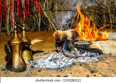 Boil the Arabic coffee on the fire in preparation for the guests, and Serving warm coffee to guests during their stay at Sheikh Zayed Heritage Festival in Abu Dhabi, UAE on 17/01/2017