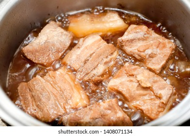 Boil the pork in a pot. Japanese food,Okinawa cuisine Rafuthy. Okinawan-style stewed pork cubes, pork belly, stewed in awamori, soy, dashi broth, and sugar.