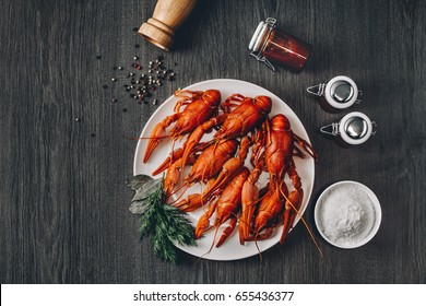 Boiled big red fresh crawfish in white plate with green herbs. Salt bowl, sauce jars and pepper grains around. Gray wooden background. Instagram vintage toning effect. Top view. Copy space.