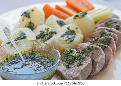 Boiled bovine tongue and a glass bowl with parsley sauce.