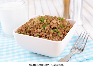 Boiled buckwheat in bowl on table close-up