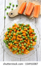 Boiled carrots with green peas in  glass bowl