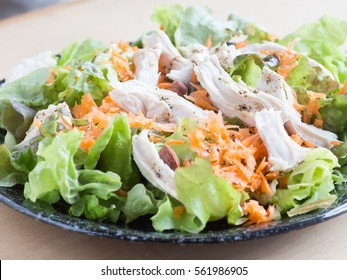 Boiled chicken brest, shredded carrots and lettuce salad on the dish