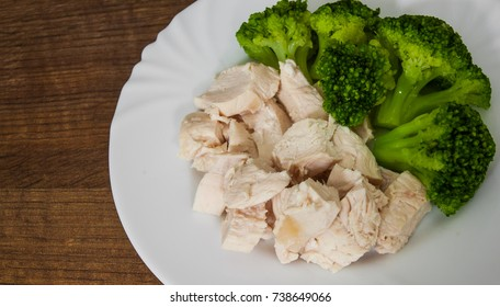 boiled chicken fillet with broccoli on wooden background.