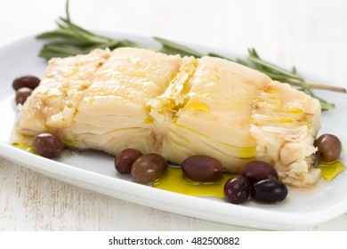 boiled cod fish with olives on white plate