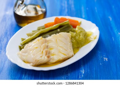 boiled cod fish with vegetables on white dish