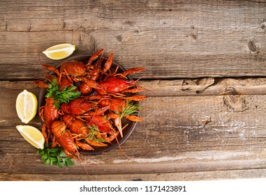Boiled cooked crayfish crawfish ready to eat onold rustic wooden background. Copy space. Overhead. Top view.