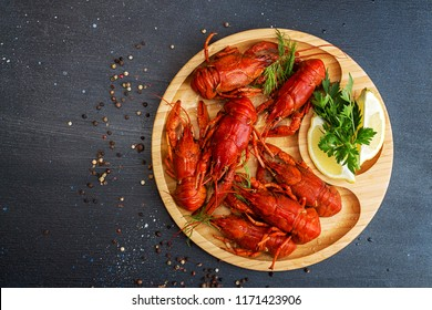 Boiled cooked crayfish crawfish ready to eat on wooden plate on black background. Copy space.