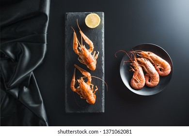 Boiled and cooked crayfish on black background,with lemon