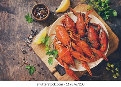Boiled crawfish, lemon and parsley on a wooden table. Appetizer protein, the concept of healthy eating. Top view flat lay background. Copy space. Toned image.