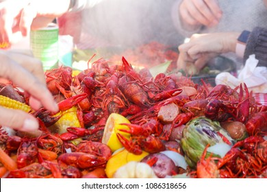 Boiled crawfish and lemons and carrots and other vegestables are piled on a table with tray for eating in background - shallow focus
