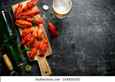 Boiled crayfish with a bottle of beer. On dark rustic background