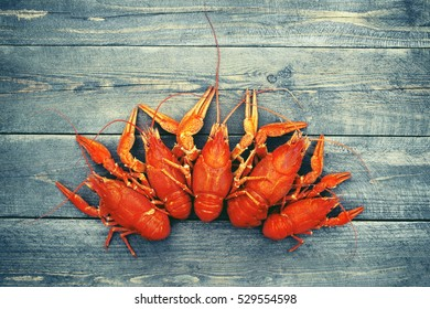 Boiled crayfish on a wooden background  in vintage color, close up