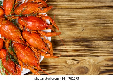 Boiled crayfish in plate on wooden table. Top view