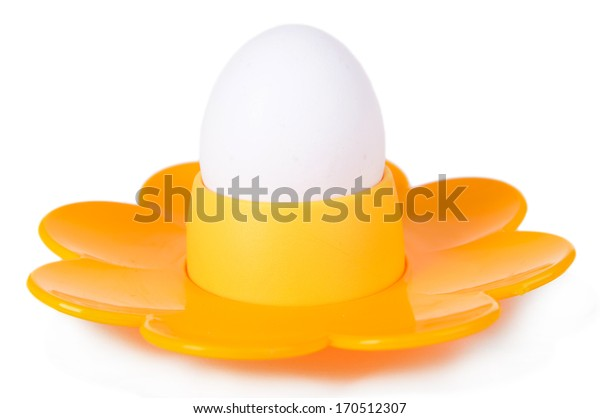 Boiled egg in egg cup isolated on white