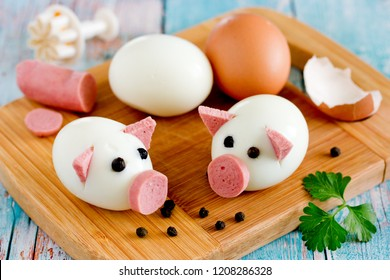 Boiled egg pigs, cute piglets made from eggs, sausage and black pepper peas, food art idea for kids
