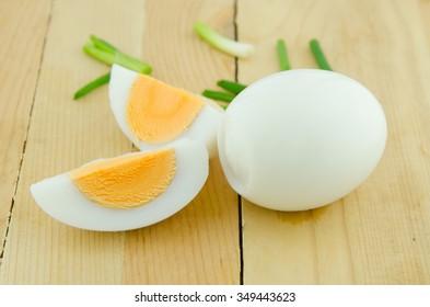 Boiled egg sliced in half and green onion leaves sliced on the boiled egg.