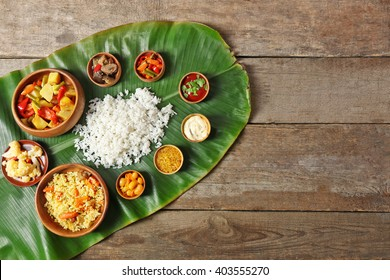 Boiled and fried rice with vegetables on banana leaf over wooden background