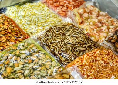 Boiled and frozen mussels in vacuum packaging. Showcase with frozen seafood.